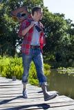 40s de sourire équipent tenir la guitare dans la marche près de l'eau Images stock