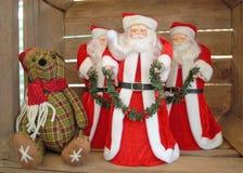 ` S de trois Santa avec un nounours à vendre sur une stalle du marché Images stock