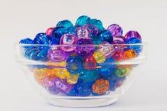 ` S dei bambini luminoso e perle variopinte visualizzate in una ciotola di vetro semplice Fotografia Stock Libera da Diritti