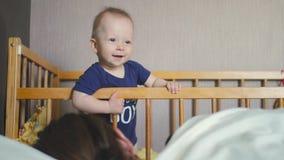 ` S del bebé que se coloca en un pesebre del bebé en casa Niño pequeño que aprende colocarse en su pesebre Sueños de la madre almacen de video