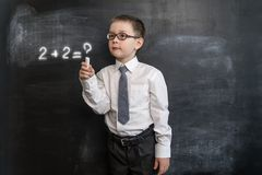 ` S del ragazzino che risolve espressione del ` s di per la matematica Di nuovo al concetto del banco Realtà aumentata Ragazzo pr Fotografia Stock
