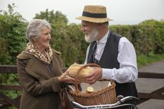 1940s delivery man and elderly house wife. 1940s delivery men and elderly house wife in a rural setting stock photo