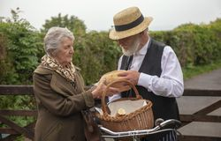 1940s delivery man and elderly house wife. 1940s delivery men and elderly house wife in a rural setting royalty free stock image