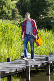 40s di camminata equipaggiano la chitarra della tenuta in parco per la ripetizione all'aperto Immagini Stock