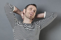 40s di pensiero equipaggiano piegare le sue armi dietro il suo collo Fotografia Stock Libera da Diritti