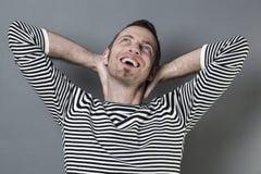 40s di risata equipaggiano piegare le sue armi dietro il suo collo Fotografia Stock