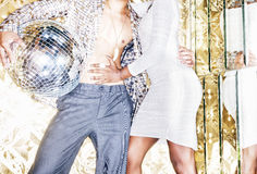 70s disco style couple posing with mirror ball Stock Photo