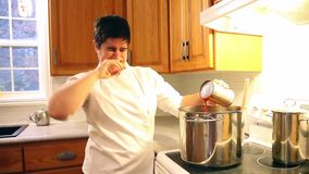 That`s disgusting- bad sauce. Chef pours a can of something stinky into a big pot on the stove stock video