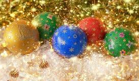 ` S do ano novo, do Natal vida ainda Verdes decorados feitos a mão, vermelho, blau, bolas amarelas showflocken dentro no ouropel  Imagem de Stock