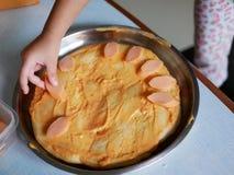 ` S do bebê pouca mão que coloca uma fatia de salsicha em uma massa da pizza imagens de stock