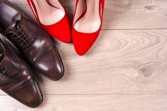 ` S dos homens e sapatas das mulheres vermelhas do salto alto no fundo branco fotos de stock