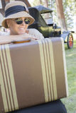 1920s Dressed Girl With Suitcase Near Vintage Car. Pretty 1920s Dressed Girl With Suitcase With Room For Text Near Vintage Car and Cabin Royalty Free Stock Image