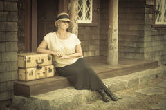 1920s Dressed Girl and Suitcases on Porch with Vintage Effect Royalty Free Stock Photos