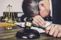 S?dzi m?oteczek z prawnikami, m?oteczek na drewnianym stole i prawniku doradcy lub samiec jest zm?czonych i migreny migrenami pod zdjęcie royalty free
