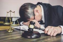 S?dzi m?oteczek z prawnikami, m?oteczek na drewnianym stole i prawniku doradcy lub samiec jest zm?czonych i migreny migrenami pod obraz royalty free