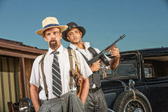 1920s Era Gangster Partners. Tough gangster with hands in pockets with armed guard Royalty Free Stock Images