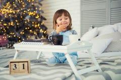 ` S Eve del Año Nuevo, el 31 de diciembre Niña linda en pijama con la taza cerca del árbol de navidad Imagen de archivo