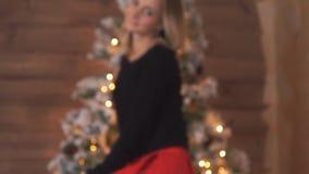 ` S Eve del Año Nuevo, la muchacha el árbol de navidad y la chimenea en los cuales las velas encendidas, celebración de la mujer almacen de video
