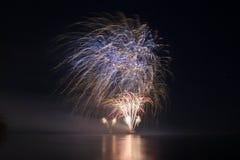 ` S Eve Fireworks för det nya året lanserade från vattnet med reflexioner royaltyfri fotografi