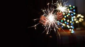 ` S Eve, luces de Bengala, bokeh colorido, manos, hombre, nueva Y del Año Nuevo Imagen de archivo libre de regalías