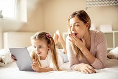 She`s excited about technology, but Mom is asleep. Mother and daughter using digital tablet stock images