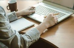 ` S för den unga kvinnan räcker arbete på en bärbar dator Royaltyfri Fotografi