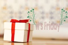 It`s friday message with white gift box with red ribbon on wood background. It`s friday message with white gift box red ribbon on wood background royalty free stock photography
