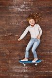 It`s fun being a kid. Girl on a skateboard, lying on the floor, looking at camera and smiling royalty free stock images