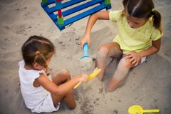 It`s fun to play in the sand. Two little girls playing in sand together. Close up stock photo