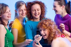 That's so funny. Five beautiful girls are reading a text message on the mobilephone Stock Photo