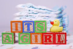 It's a girl. Spelled out in blocks with a rubber duck, diapers in the background Royalty Free Stock Photography