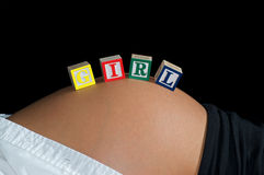 It's a GIRL 2. Young mother reclining in front of a black background with GIRL spelled out with child's toy blocks Stock Photography
