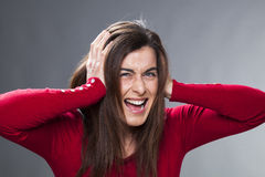 30's girl getting mad, suffering from migraine, covering her ears with her hands Royalty Free Stock Photos