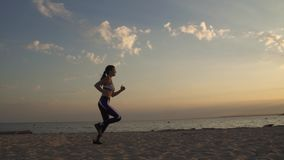 20s girl running on the sand on the beach at sunset. Jogging outdoors. Portrait of a sportswoman running on the beach at sunset stock video footage