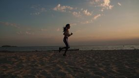 20s girl running on the sand on the beach at sunset. Jogging outdoors. slow motion. Portrait of a sportswoman running on the beach at sunset stock video footage