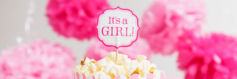 It`s a girl sign in a popcorn bag at the baby shower party.  Paper flowers background.  Baby shower celebration concept Royalty Free Stock Images