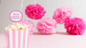 It`s a girl sign in a popcorn bag at the baby shower party.  Paper flowers background.  Baby shower celebration concept Royalty Free Stock Photography