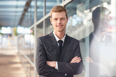 He's got will and attitude to succeed in business. Portrait of a confident and successful businessman standing with his arms crossed outside leaning against the royalty free stock photo