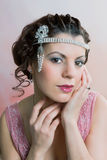 1920s hair and headband. Closeup in vintage colors of a 1920s style young woman with diamond headdress and flapper dress stock photo