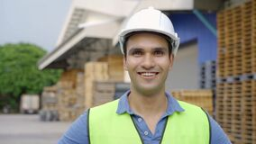 20s happy Indian distribution shipping depot worker looking at camera and smile. Male worker in hard helmet at
