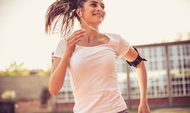 She`s happy when she`s exercising. Young happy woman running. Close up royalty free stock images