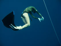 It's hard to take deep freediving photos. Freediver tries to take underwater photos while standing at the same depth stock image