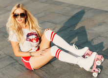 She`s a head turner. A looker leggy long-haired young blonde woman in a vintage roller skates, sunglasses, T-shirt shorts sitting Royalty Free Stock Photos