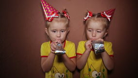It`s a holiday. Two charming little twin sisters in red dresses and cone-shaped caps on their heads are blowing into. Unfolding tubes stock video footage