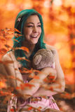 She`s hugging. Teddy bear, happy smile, blue hair, wood stock image