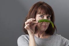 50s infelici maturano la donna che mette in discussione il gusto di peperone verde Fotografie Stock