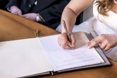 S'inscrire de signature de jeune mariée de mariage, stylo de participation et couples élégants de mariage de document officiel Photographie stock libre de droits