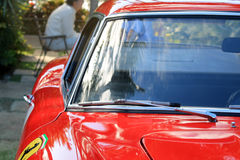 1950s italian sports car. 1950s Ferrari 250 GT closeup details. people seating and talking in the background. sdof Royalty Free Stock Image
