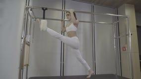 S-journal Pilates aerobisk instruktörkvinna i cadillac konditionövning gör splits till stock video