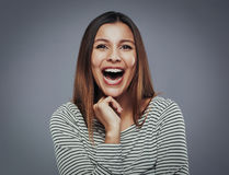 That`s just too funny. Beautiful young woman laghing out loud against a gray background Stock Images